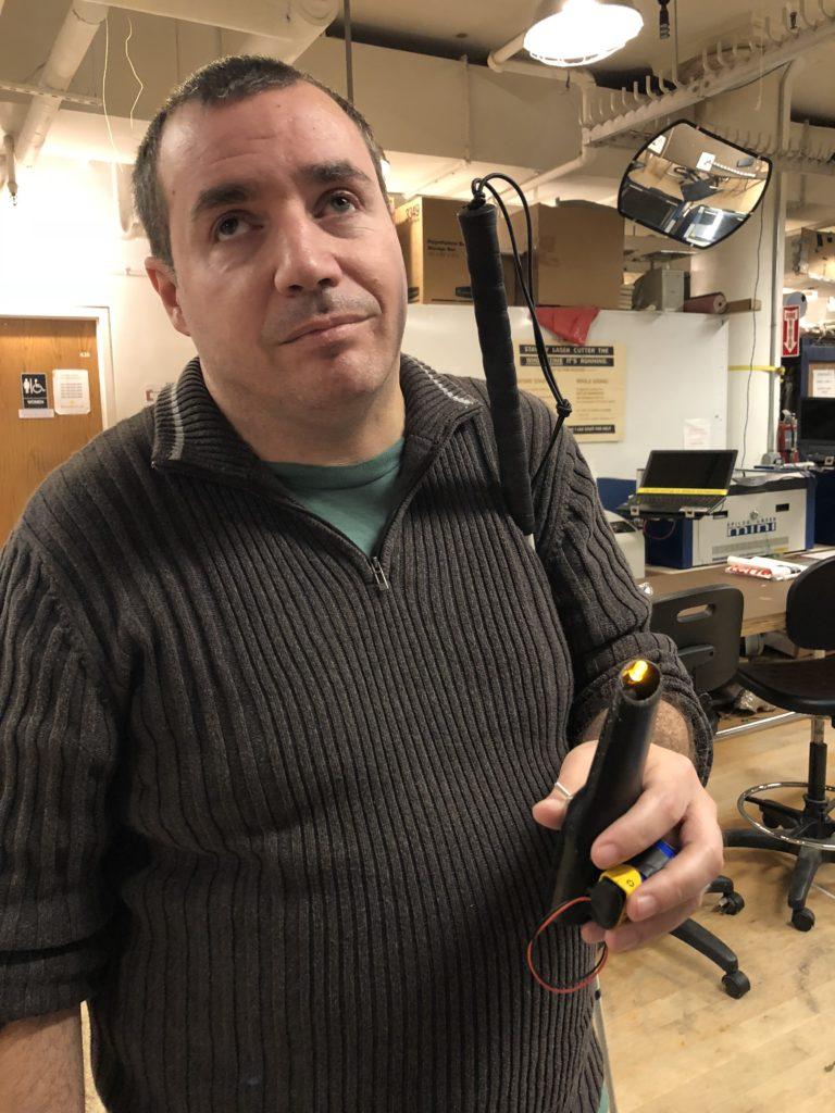 Antonio holds the flashlight in his hand