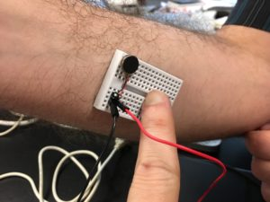 Antonio holding mini breadboard with button vibe motor to inner forearm, closeup.