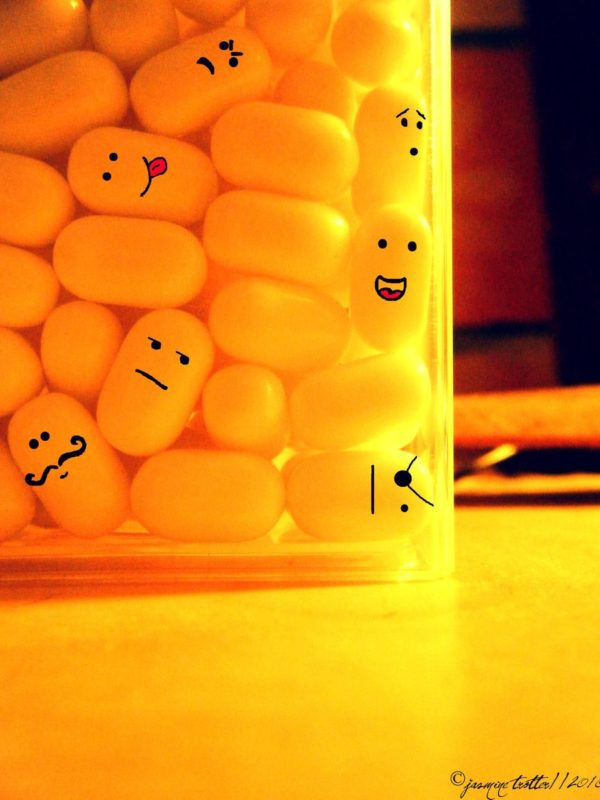 yellow tic tacs in a container with faces drown on several of them