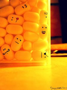 yellow tic tacs in a container with faces drown onto several of them