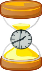 yellow hour glass timer with clock on top of it