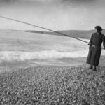 Archival Photo of woman fishing on beach