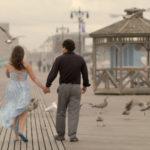 Couple walking on Coney Island boardwalk