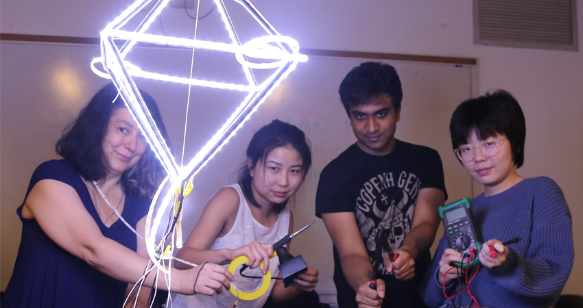 ITP Camp attendees brandishing tools behind a glowing diamond made from LED lights