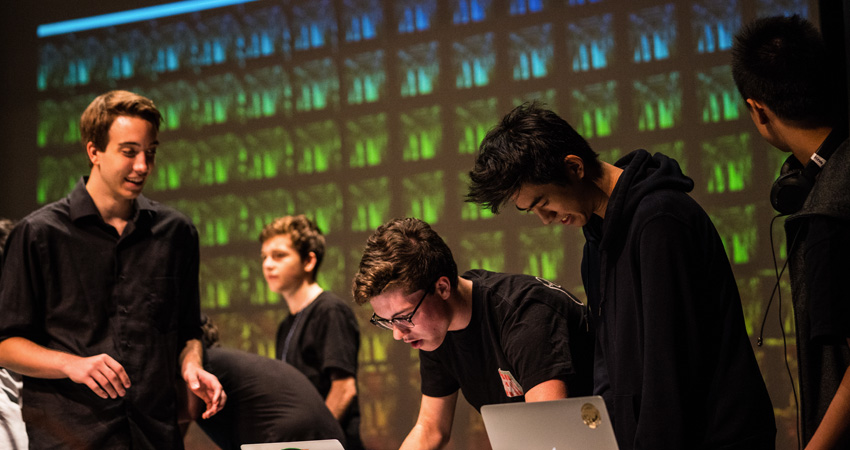 Student musicians working on laptops while onstage