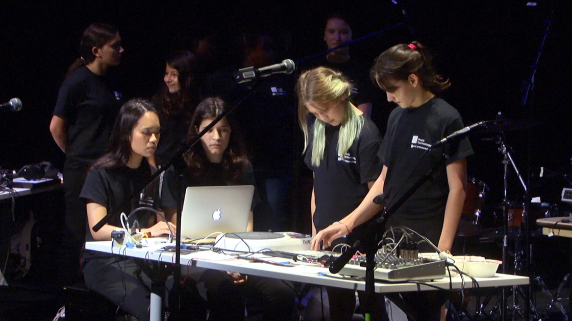 GEMS performers on stage working with electronic instruments and equipment