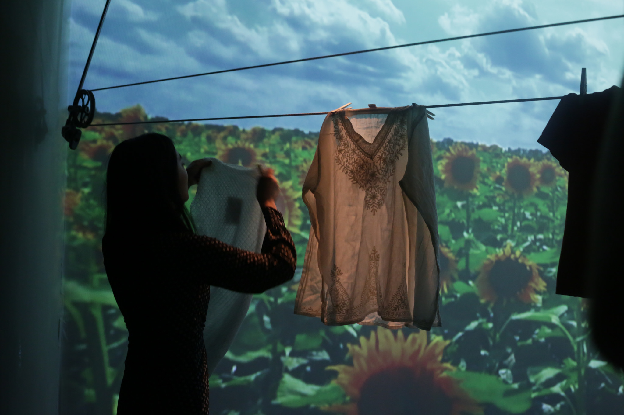 Woman hanging laundry in front of a projected field of sunflowers