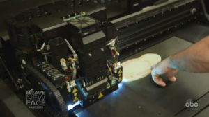 man pointing to a 3D print in progress