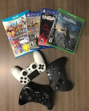 four video game boxes and three controllers