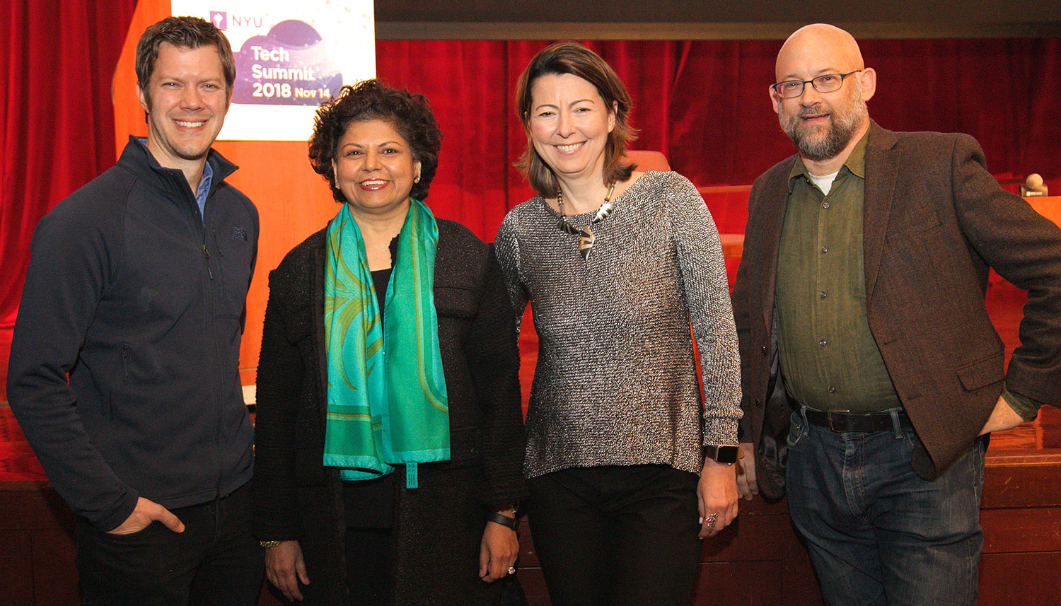 Speakers posing in front of a red curtain