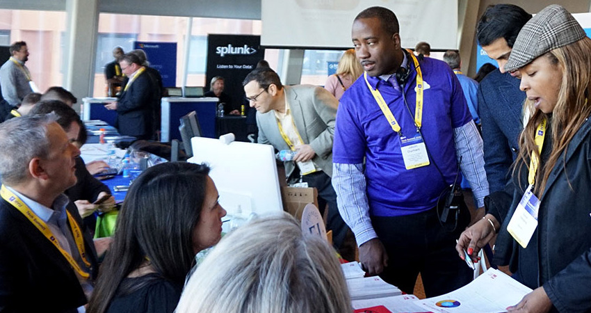 attendees at a vendor table at the NYU Technology Summit
