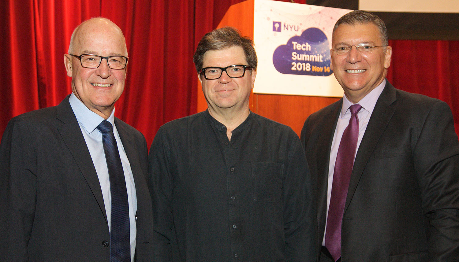 NYU President Andy Hamilton, keynote speaker Yann LeCun, and NYU CIO Len Peters in front of a red curtain at the NYU Technology Summit