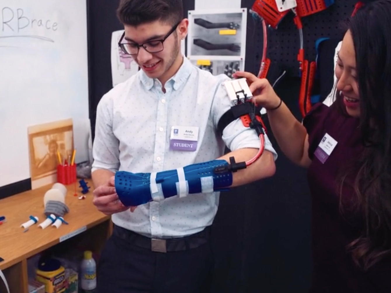 student at a showcase trying on the prototype brace