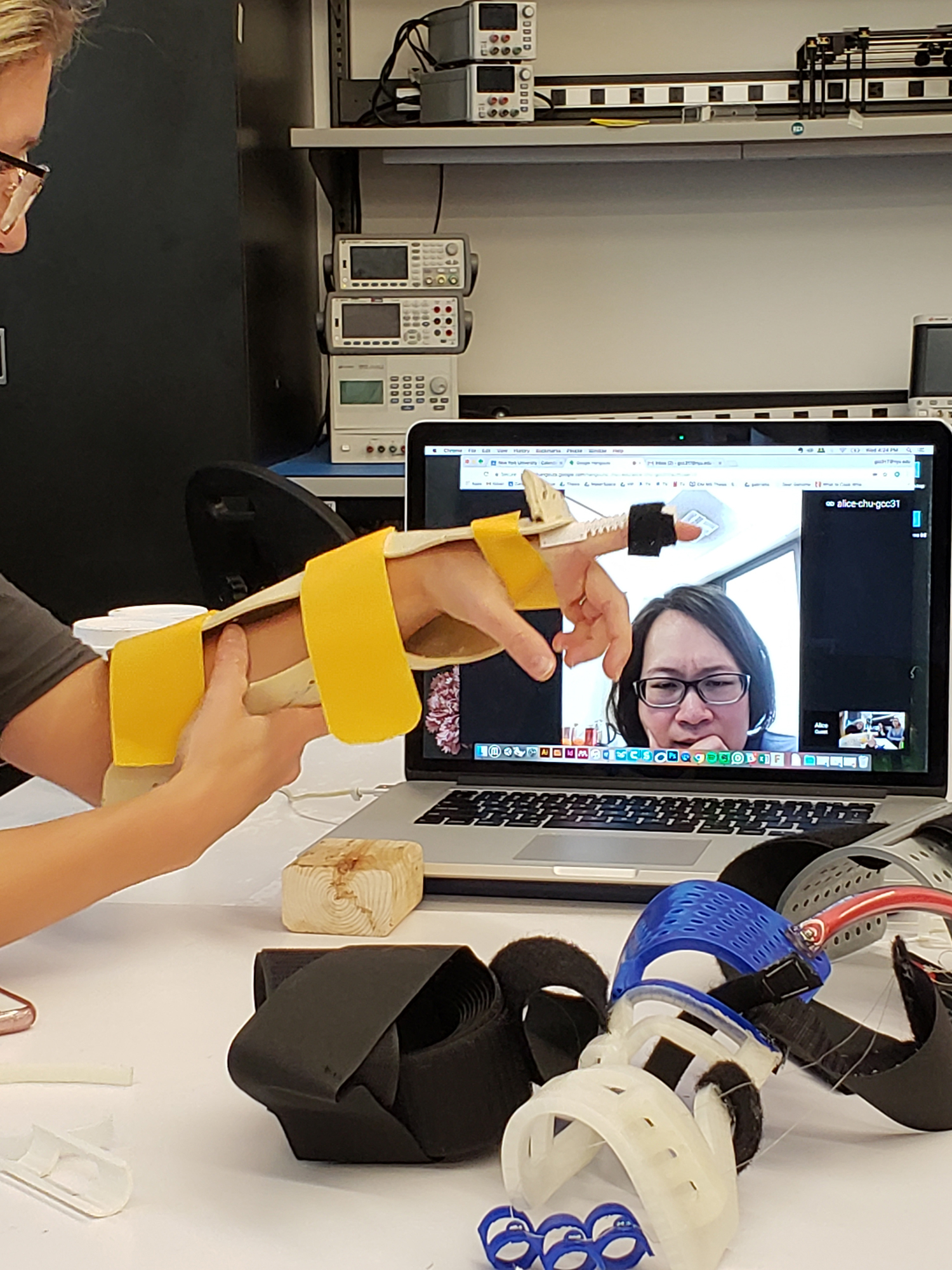a researcher wearing a prototype brace while video chatting with a remote colleague via laptop