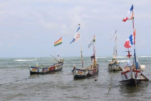 fishing boats with flags on the ocean