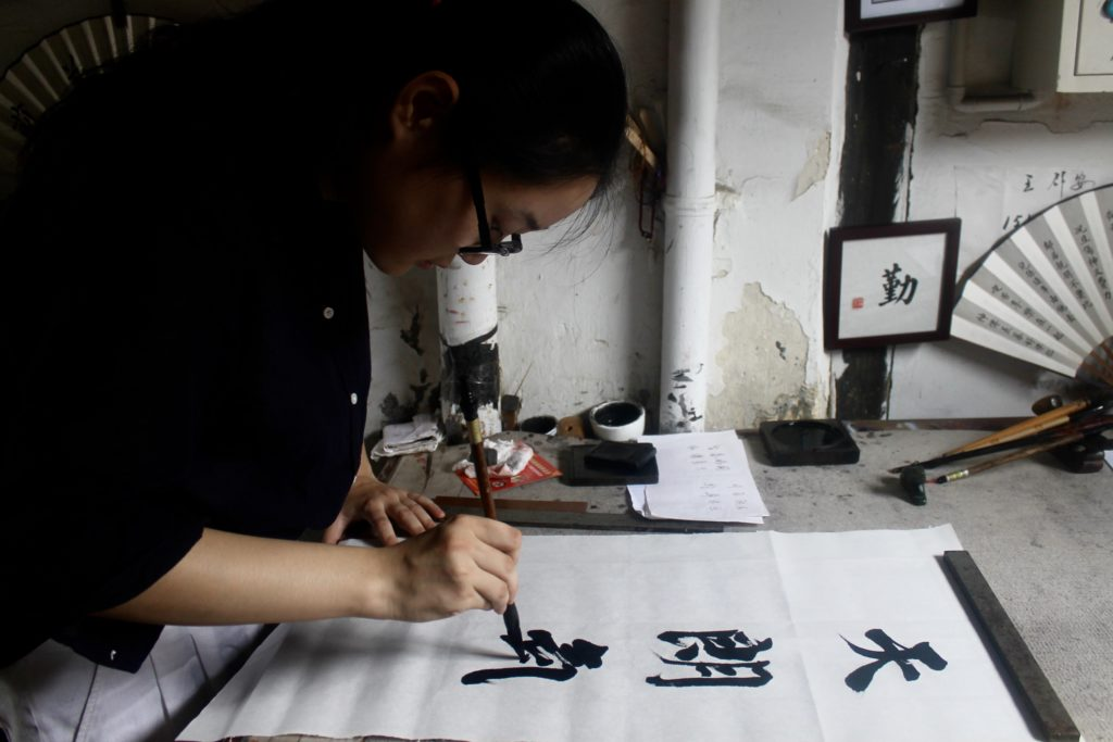 woman writing in Chinese calligraphy