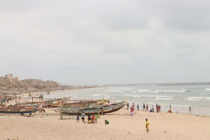 people standing near fishing canoes on beach
