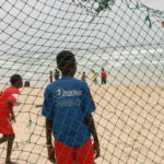 children on beach seen through soccer goal net