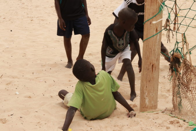 close-up of children playing soccer on sand