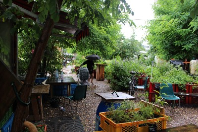 An urban garden space full of green plants, tables, and chairs.