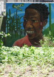 Painting of a woman with dark skin displayed in a sunny green garden.