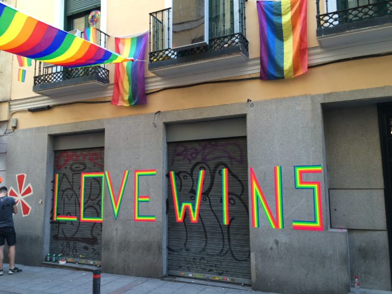 "A concrete building with ""love wins"" painted on the side in colorful paint, also displaying rainbow flags."