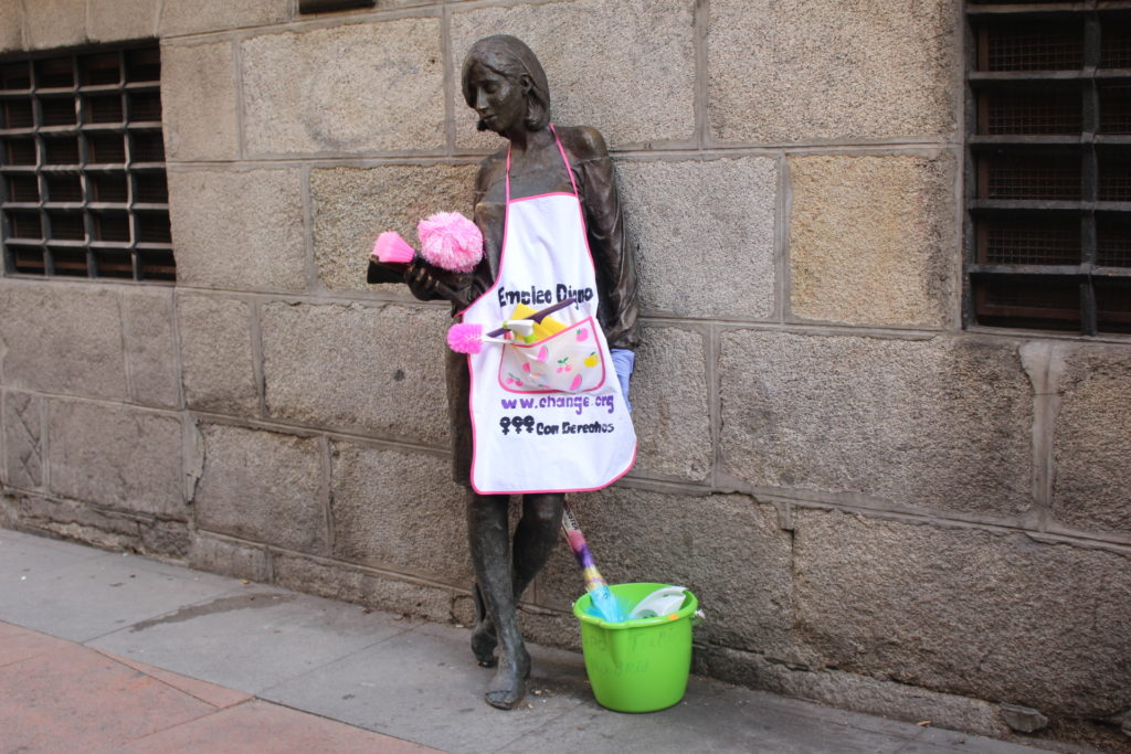 Bronze statue of a lady garnished with an apron and cleaning supplies.