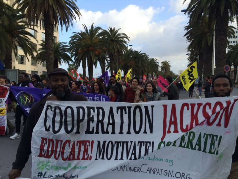 People marching and holding up banner for Cooperation Jackson