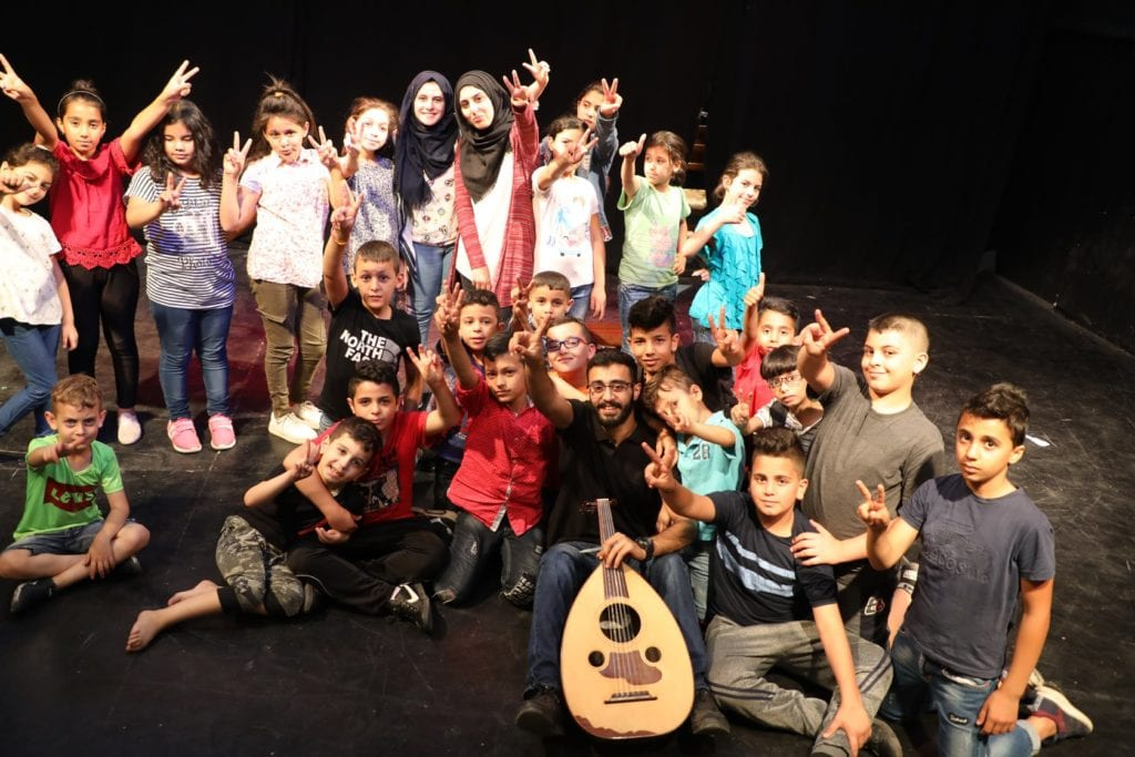 large group of children and man with guitar posing onstage giving peace sign