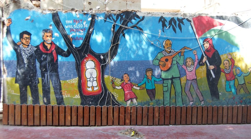 mural showing people playing music around a tree