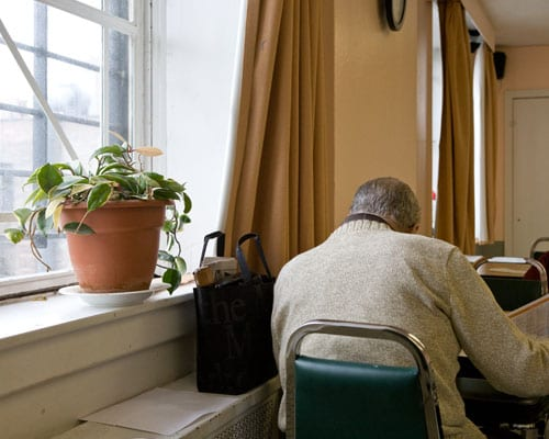 A man facing away from the camera reading a newspaper sitting on a green chair by the window where there's a green potted plants
