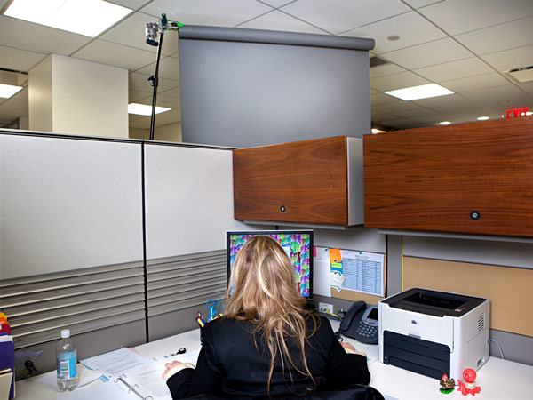 A woman working in a cubicle staring at a screen