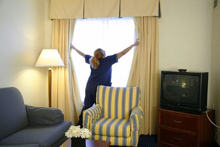 A woman drawing apart the curtains during daytime. Also features a yellow and blue striped couch and a blue couch by an old TV set on a cabinet.