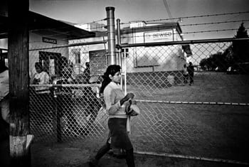 A black and white photo of a girl walking in front of a fence