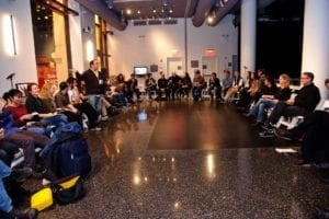 Various people sit in chairs in a U shape, in the gallery space.