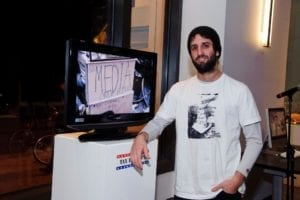 """Man with beard and beanie pose against a monitor on a pedestal in the gallery space with the a still shot of a protest sign stating"""" media"""""""
