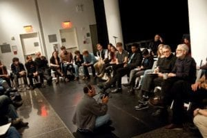 Videographer kneels to record man as he speaks in gallery space amongst others seated in chairs.