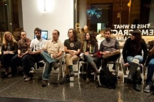 Various men and women sit in gallery space and participate in a group discussion.