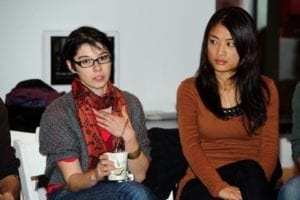 Woman with red scarf speaks as woman in tan sweater listens beside her.