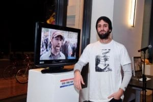 Man with white T-shit and black beanie poses against a pedestal with a monitor on top with a still shot of a man speaking during a protest.