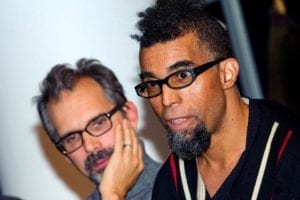 Portrait of artist Dread Scott and another man with glasses and beard in the gallery space.