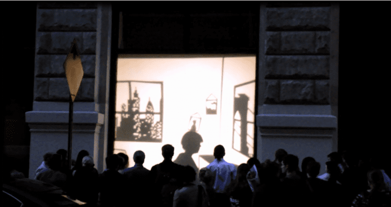 The screening of a film on a window being watch by onlookers