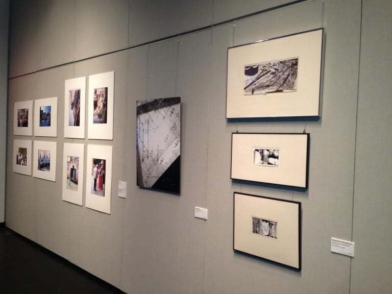 An angled photo of the gallery wall featured one central photo surrounded by two collages: a group of 4 squares and three rectangles framed and placed one below the other