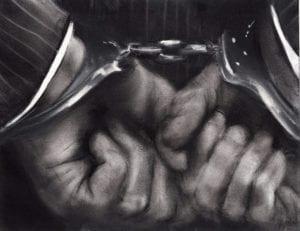 Close up shot in black & white of black hands cuffed