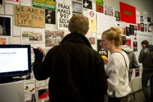 Man and woman converse while looking at artwork on gallery wall