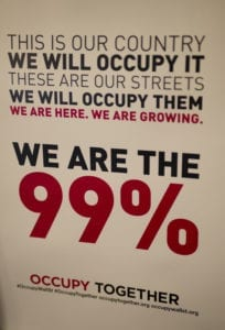 """Close up of poster with red and black font stating """"THIS IS OUR COUNTRY WE WILL OCCUPY IT THESE ARE OUR STREETS WE WILL OCCUPY THEM WE ARE HERE. WE ARE GROWING. WE ARE THE 99%"""""""