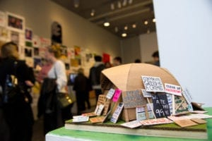 Installation of mini protest signs surrounding a cardboard sculpture on a pedestal in gallery space