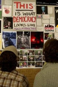 Two people gaze at Dread Scott's artwork on gallery wall