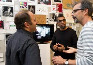 Two white men converse in gallery space with artist Dread Scott