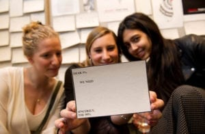 """Three white women pose with smiles as the woman in the center holds a postcard to the camera that says"""" Dear 1%, We Need ,,, Sincerely The 99%"""